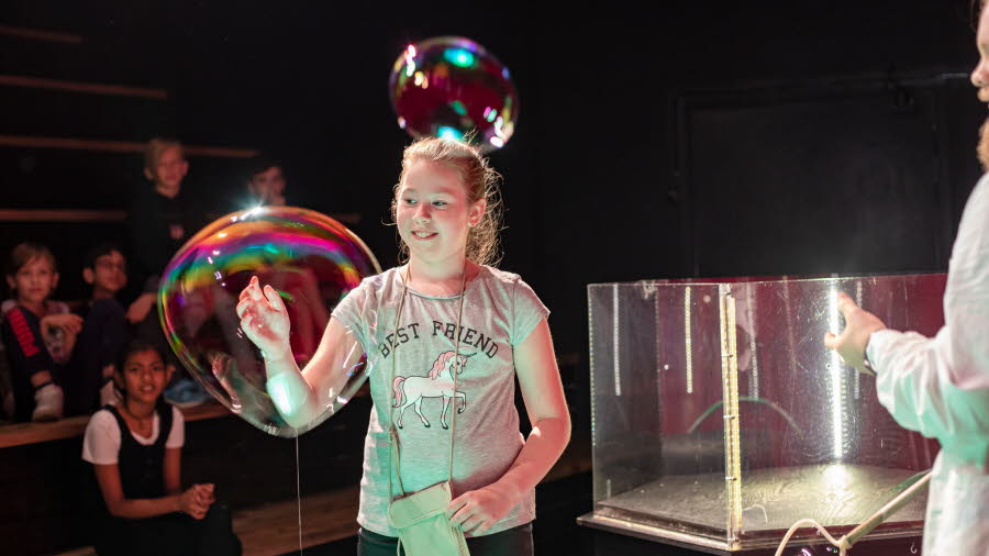 A girl is looking at soap bubbles